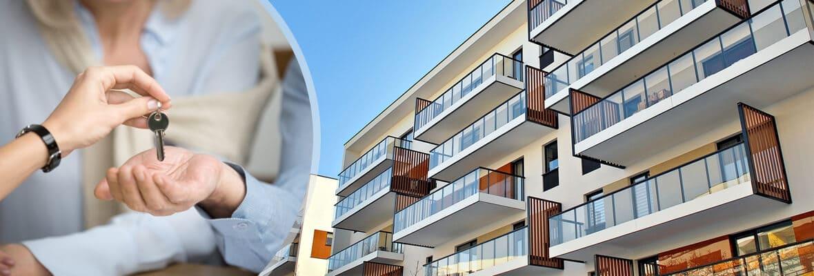 鍵を出す女性と高級なマンション